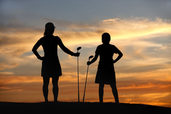 Silhouette of two women standing with golf clubs in their hands