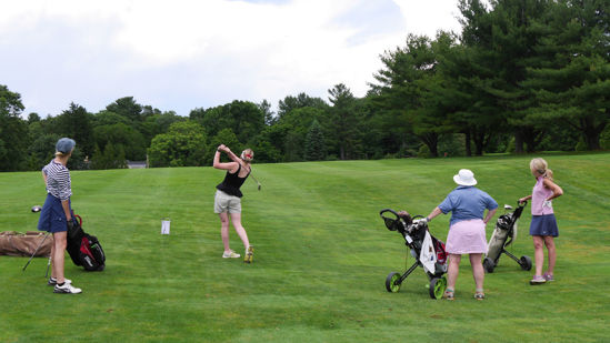 Female golfer takes a shot on the fairway while three other female golfers watch